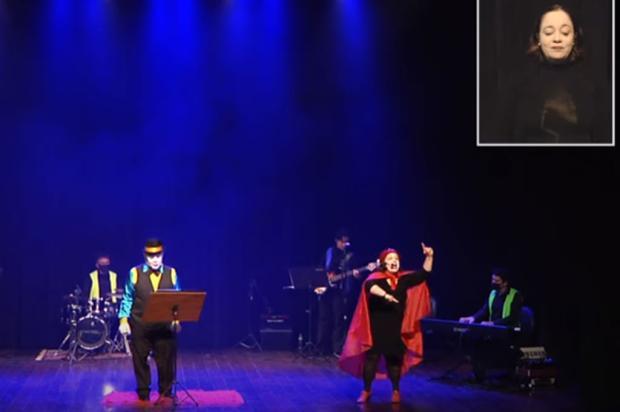 A imagem mostra aristas com deficiência encenando uma peça em cima do palco. No canto direito um janela com o intérprete de livras