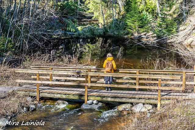 Nainen seisoo sillalla lammen päällä