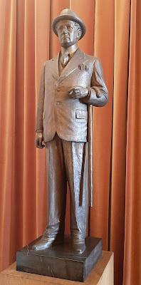 escultura de homem com bengala e cigarro