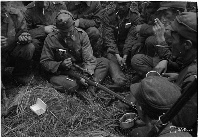 Finnish soldiers inspecting a Soviet Mosin-Nagant sniper rifle, 14 August 1941 worldwartwo.filminspector.com