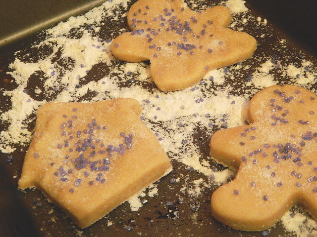 Cookie dough cut into shapes on a pan with flour on it