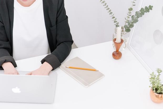 Mulher do pescoço para baixo sentada à mesa com seu notebook trabalhando