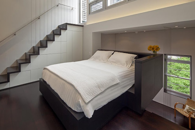 Modern king sized bed by the staircase