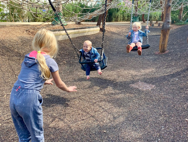 Older child pushing baby on swing with a 3 year old behind also on a swing