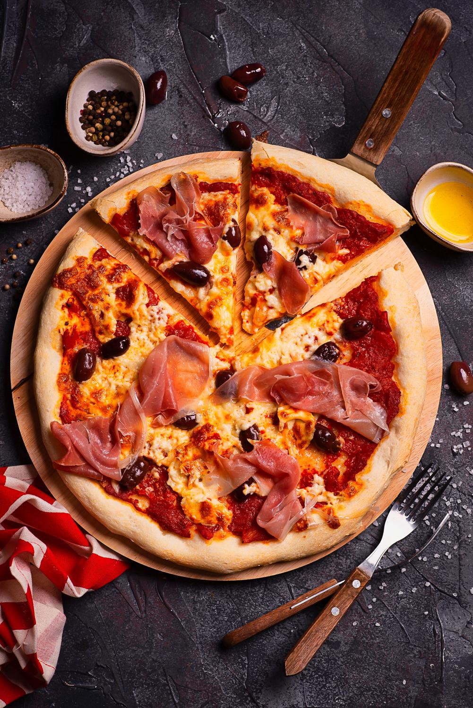 Domowa pizza z szynką parmeńską, oliwkami i mozzarellą