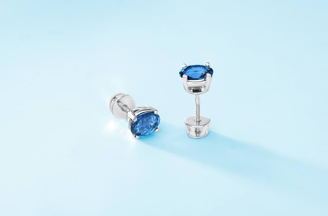 A pair of blue stud earrings resting on a light blue surface.