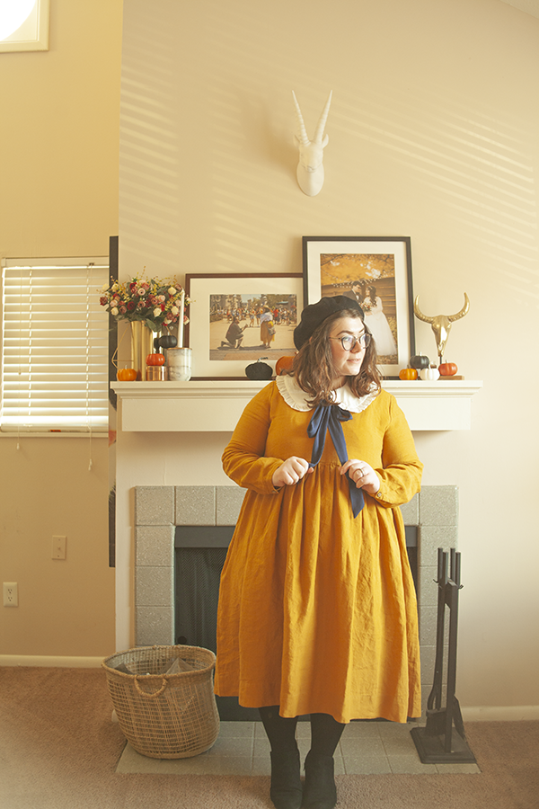 An outfit consisting of a black beret, a white oversized peter pan collar with a navy ribbon tied in a bow under it, yellow baby doll linen dress and black tights and ankle boots.