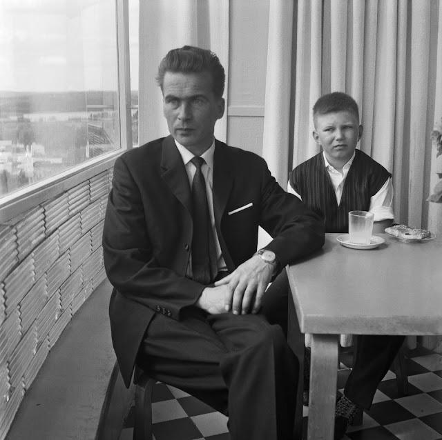 Mies ja poika istuvat pöydän ääressä vesitornin kahvilassa, mies katsoo ulos ikkunasta ja pojan edessä on maitolasi ja viineri.