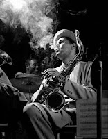 A black and white photo of Jazz Saxophonist Dexter Gordon. He is smoking and holding his saxophone.
