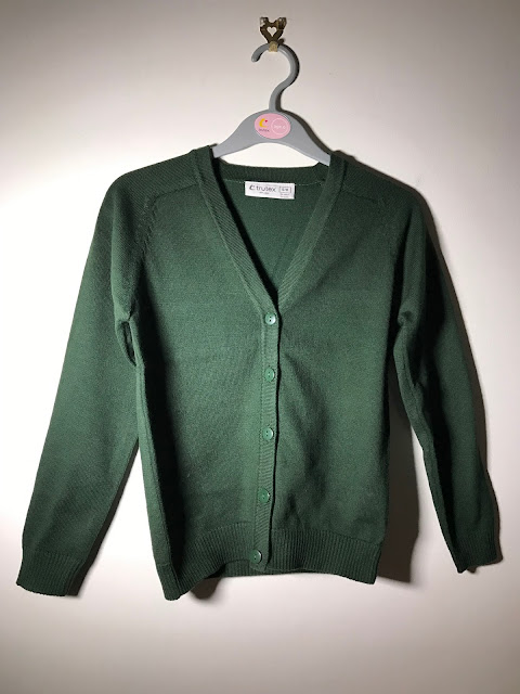 A dark green cardigan on a hanger in front of a white wall