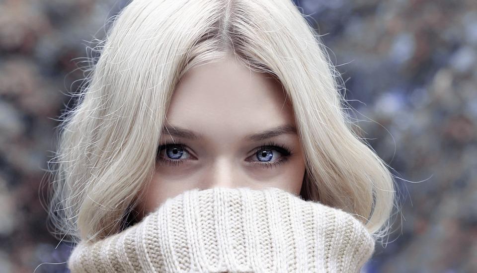 pretty blonde peering over her sweater.jpeg