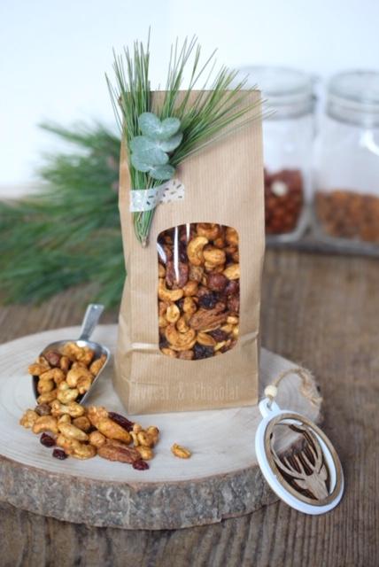 """alt=""""mélange de noix épicées présentées dans un joli sachet en craft, décoré d'une branche de sapin"""""""