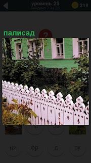 Около дома сделан палисад, розового цвета резной забор с узорами