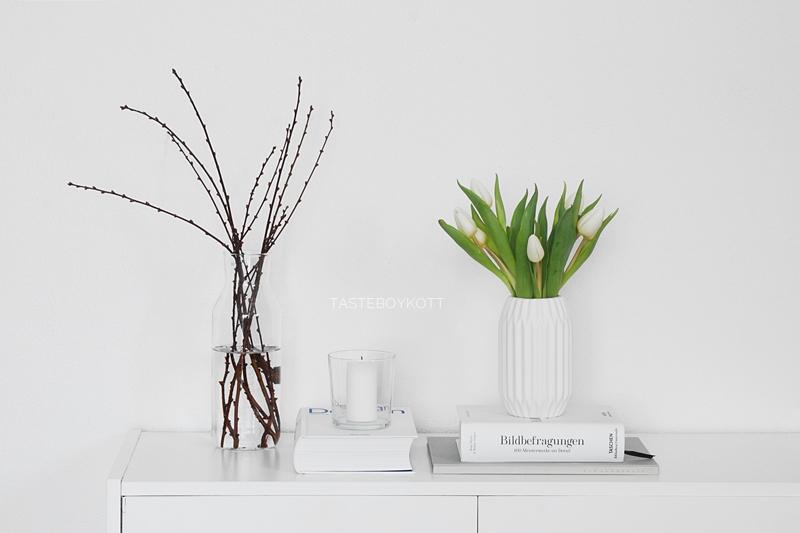 Schlichte Frühlingsdeko mit weißen Tulpen in Origami-Vase, Zweigen in Glasvase, Kerze und Büchern. Tasteboykott Wohnblog.