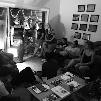 Image of a Split This Rock house party. People sit in a living room facing a poet sharing a poem.