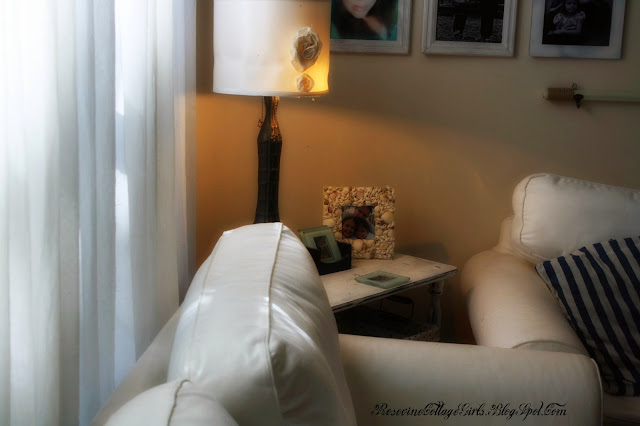 photo of a sea side living room white couches nautical striped throw pillows a picture frame with shells on it a lamp with a rose photos on the wall | rosevinecottagegirls.com