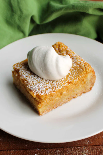 pumpkin gooey butter cake with big dollop of maple whipped cream on top