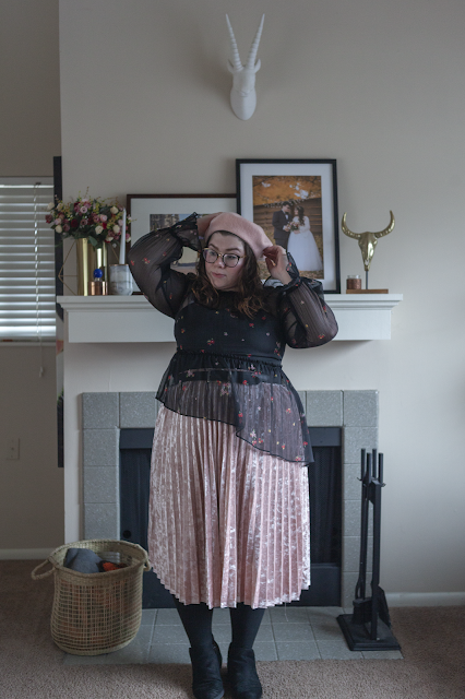 An outfit consisting of a pink beret, black sheer floral dress tucked into a pink pleated velvet midi skirt and black ankle Chelsea boots.