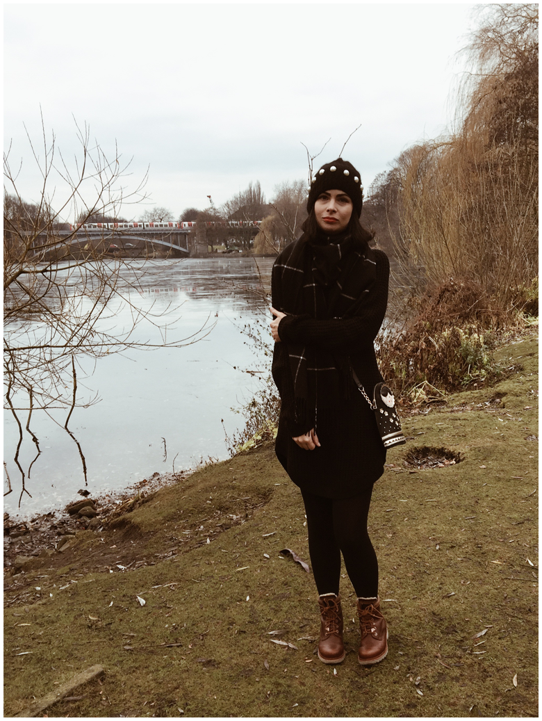 THE LAKE | June Gold wearing a black Gina Tricot dress, a black & Other Stories beanie and brown Panama Jack winter boots