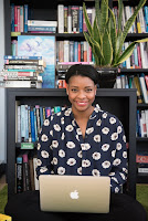 Black woman with laptop sitting in front of a bookcase