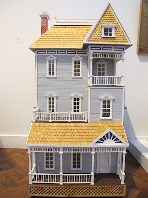 Four-story dolls' house, on display in a gallery.