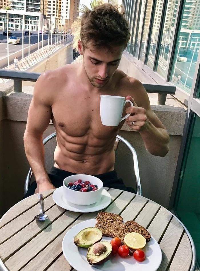 handsome-shirtless-fit-abs-blond-messy-hair-male-model-drinking-morning-coffee-tea-eating-healthy-avocados-building-view