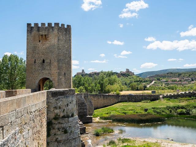 Puente medieval con torre y pueblo medieval al fondo