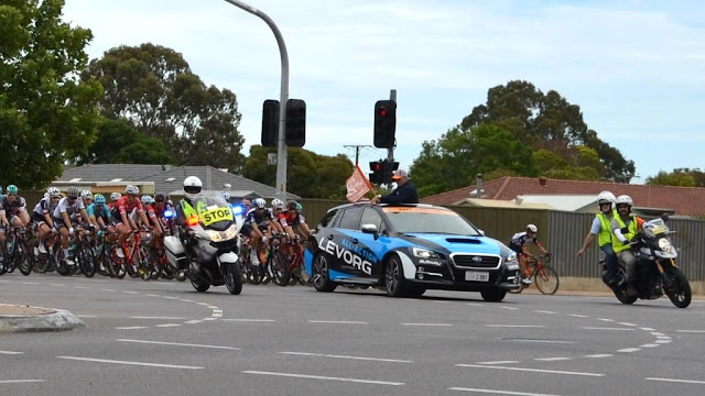 The peloton enters the crossroad intersection under escort by a police motorbike, the Race Director's car and a race support motorbike. There are single storey buildings on the far corner of the intersection behind galvanised iron fences. Traffic lights can be seen jutting up towards the cloudy sky. The profile of eucalyptus trees can be seen in the background behind the houses.