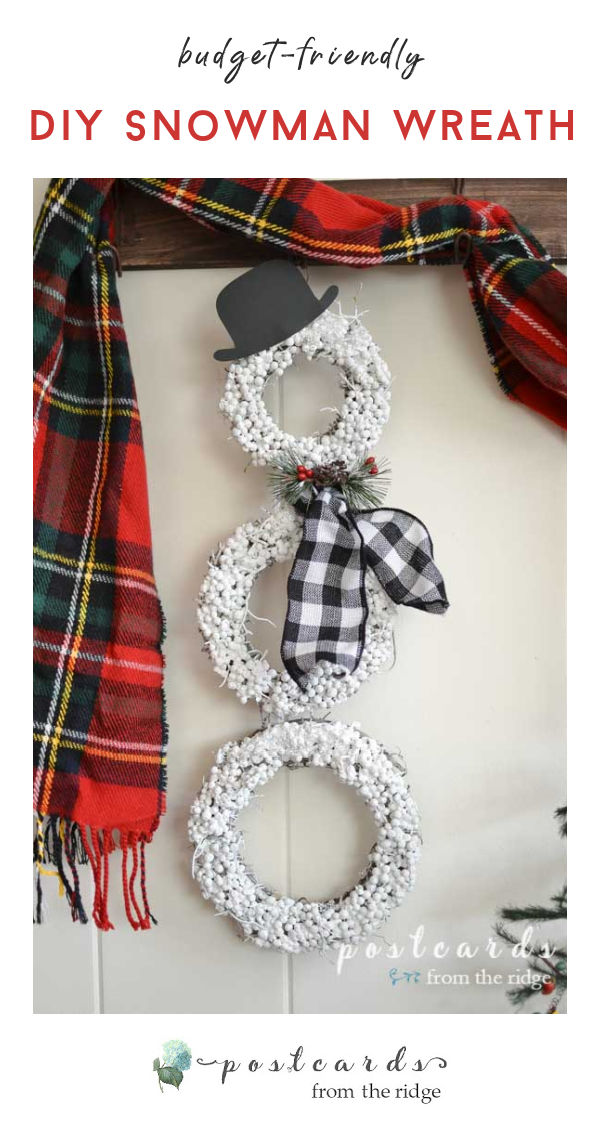 snowman wreath on wood wall rack with plaid scarf