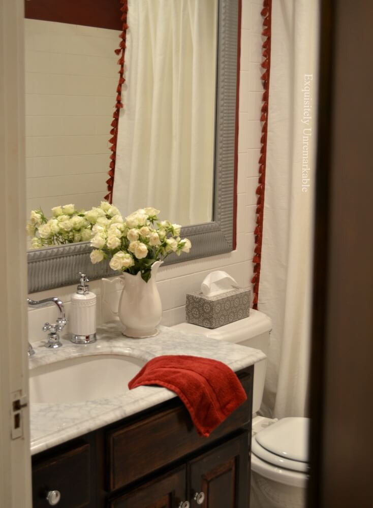 Red Cottage Style Bathroom with flower in a white pitcher on marble vanity countertop