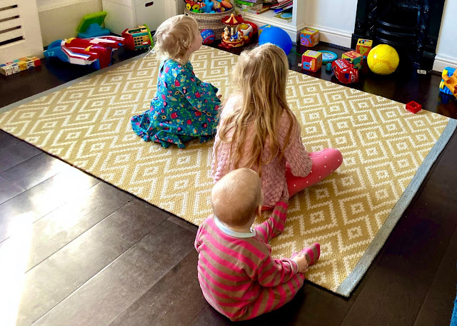 3 children sitting on the floor staring towards a TV screen that isnt in the photograph
