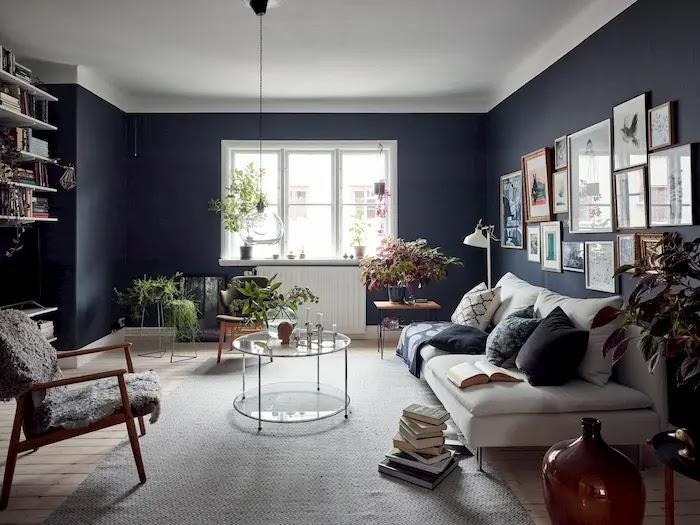 salón pintado de azul oscuro con gran galería de cuadros