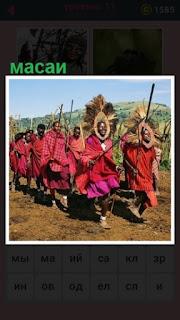 с палками в одежде идут племя масаи строем