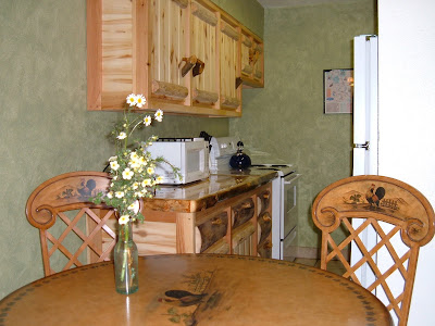 Kitchen with beautiful rustic log cabinets, tile floors, and faux green walls.  Dinning table with faux painting of a rooster.
