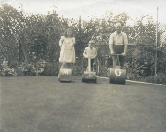 Grandad Beck with Grandchildren lining up for a race. Marion has a lawnmower with a M on it. Jackson has a lawnmower with J on it and Grandad has a lawn roller with G.