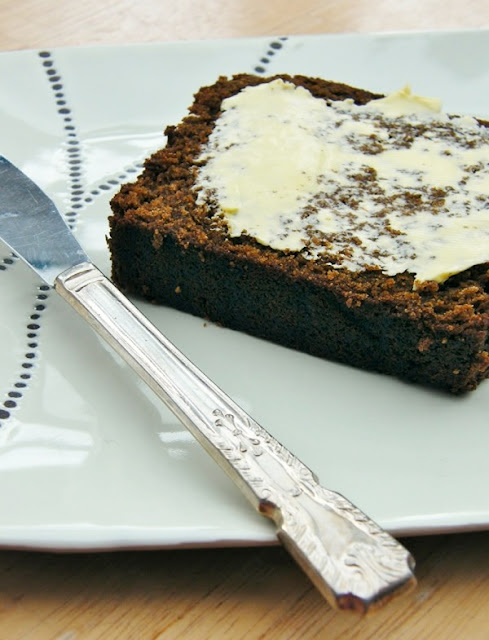 A slice of Treacle Gingerbread Loaf, spread with butter on a white plate with silver knife