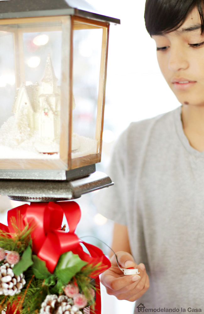 boy playing christmas songs on snow blowing lamp - Stocking holder