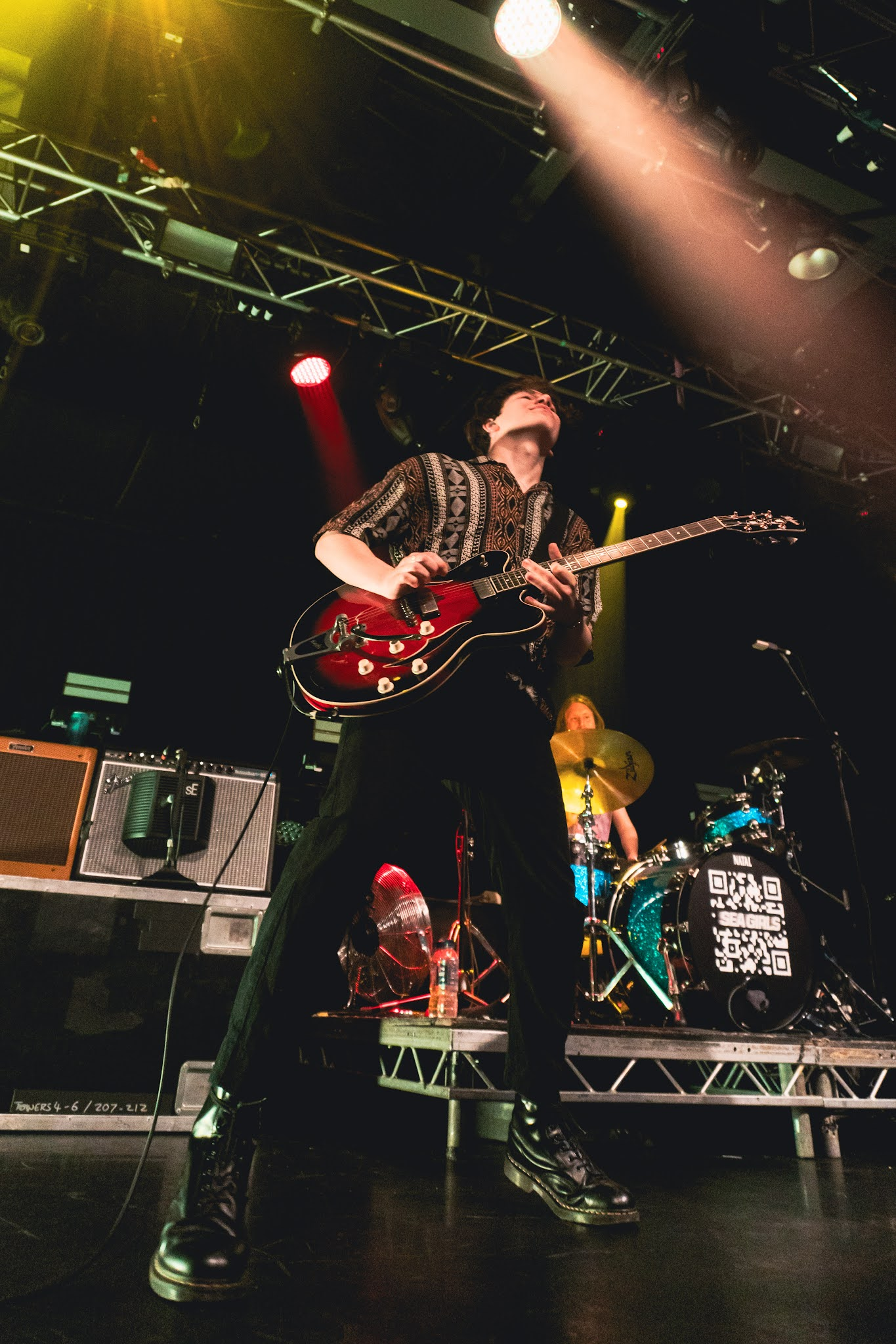 Photo of Rory (lead guitar) from Sea Girls on stage with Oli (drummer) in background