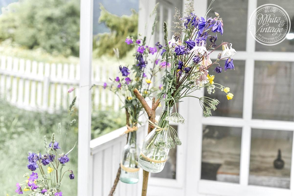 Gartendeko selbermachen aus Glasflaschen und Ästen