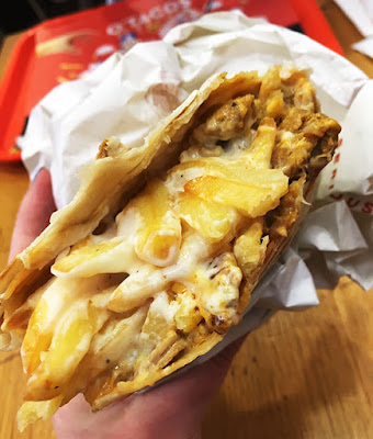A French taco from O'Tacos, bitten into to show the chips and cheese sauce