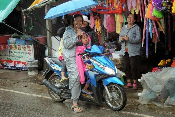Тайская мама на скутере под зонтиком