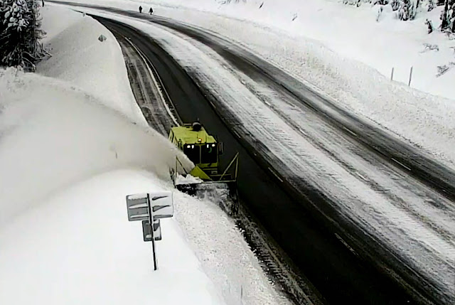 A snow blower works to clear US 2 Stevens Pass while in the distance people walk on the highway, creating potentially dangerous situations for them and vehicles.