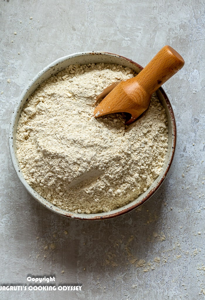 Mixed multigrain flour for roti/chapatti is in a beige bowl with a wooden scoop