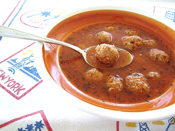 A spoon is lifting a meatball out of the bowl of Armenian meatball soup