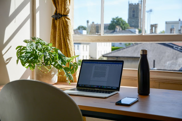 A home office set up in front of a window