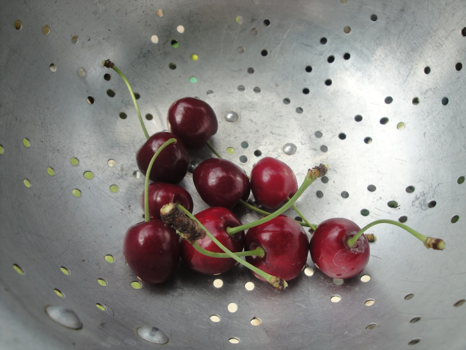 A group of cherries in a colander.