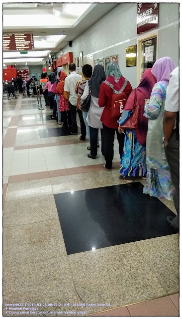 Gambar suasana ketika orang ramai beratur untuk ambil nombor giliran di Hospital Putrajaya pada waktu pagi.
