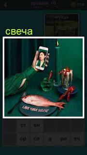 на столе доска с рыбой, в руке телефон с фото и рядом горящая свеча на канделябре