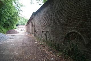 Eine lange Backsteinwand mit zugemauerten Rundbögen