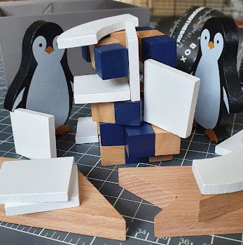Wooden Penguins and other items from The Box arranged as if playing Jenga